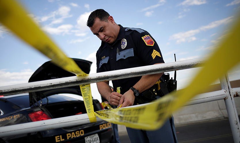 A police officer secures the area with a police cordon after a mass shooting at a Walmart in El Paso, Texas, on Aug. 3, 2019.