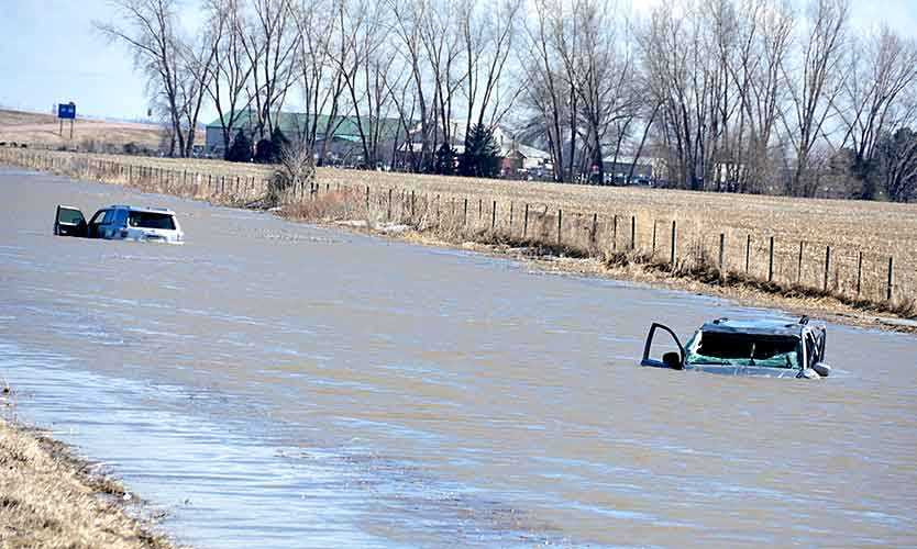 Two abandoned cars are submerged next to I-29 near Jefferson, South Dakota, after record flooding in March.