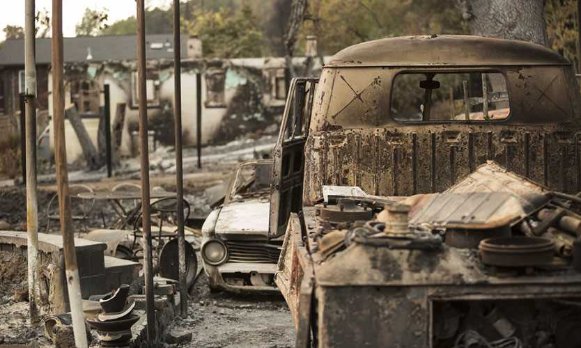 A burned car near the remains of a home in a Sonoma County neighborhood in 2017