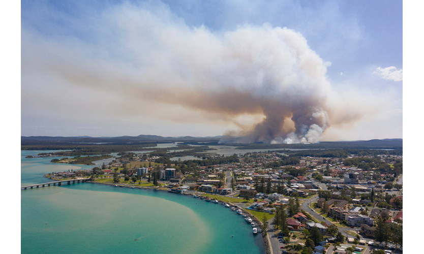 Town of Tuncurry on the New South Wales north coast with a bushfire burning in the background