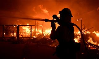 A firefighter attempts to douse flames during the Woolsey Fire in Southern California.