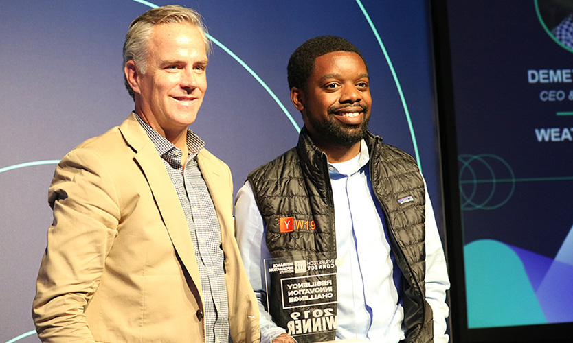 Sean Kevelighan, CEO of the III, presents the Resiliency Innovation Challenge award to Demetrius Gray of WeatherCheck.