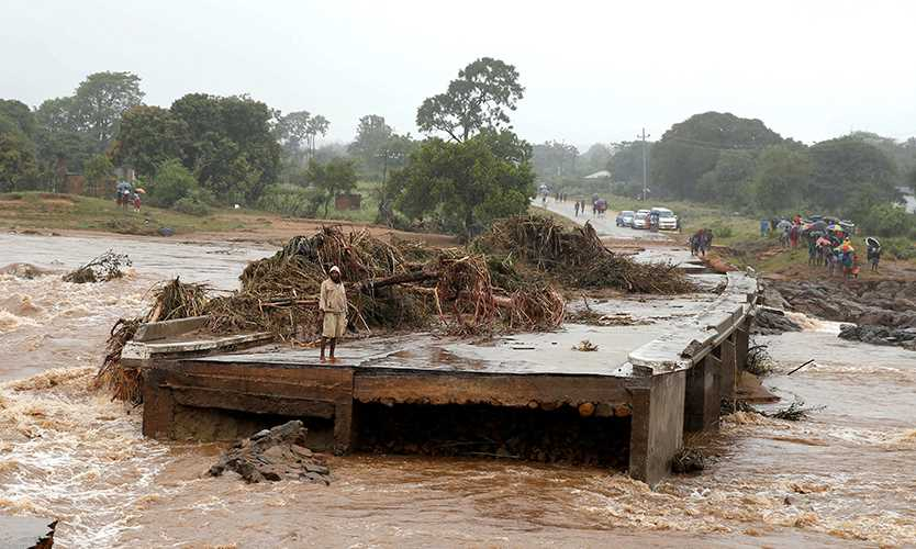 A man looks at a washed away bridge along the Umvumvu River following Cyclone Idai in Zimbabwe.