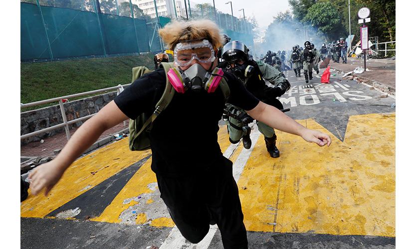 A university student runs from riot police at the Chinese University of Hong Kong, Nov. 12, 2019.
