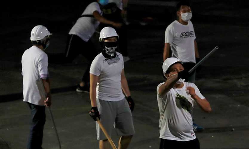 Men in white T-shirts with poles are seen in Yuen Long after attacking anti-extradition bill demonstrators at a train station in Hong Kong